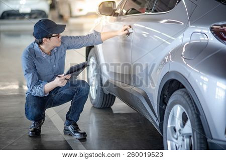 Asian Auto Mechanic Holding Car Door Handle And Digital Tablet Checking The Car In Auto Service Gara