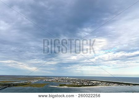 Aerial view of a island with dramatic blue sky.