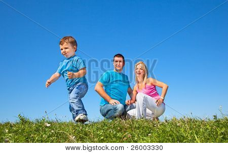 Happy family having fan in park on sunny day under the clear blue sky
