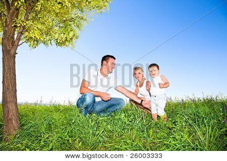 Gelukkige familie op picknick in het park onder boom