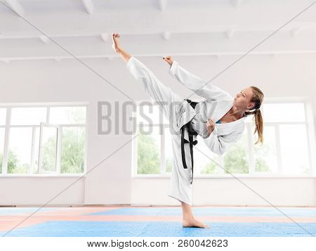 Young Active Girl Wearing In White Kimono With Black Belt Performing Martial Arts High Kick Skill. S