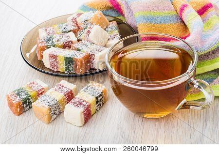 Multicolor Rakhat-lukum In Saucer, Cup Of Tea, Napkin On Wooden Table