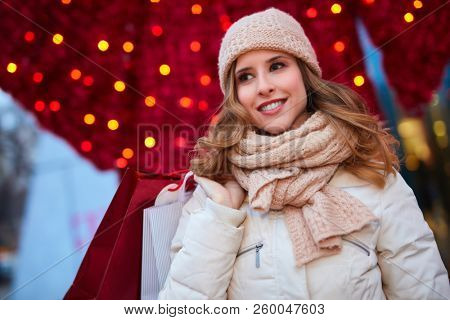 Woman shopping for Christmas. Young happy woman holding christmas decorated shopping bags in front of christmas lights.