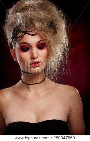 Spooky woman in halloween makeup looking down.