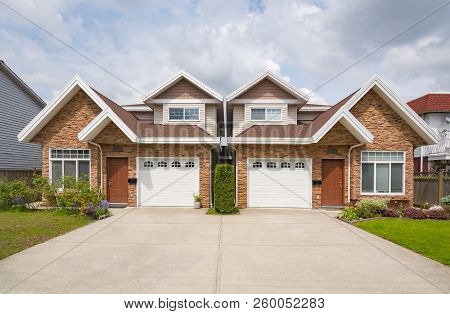 Residential Duplex House With Concrete Drive Way And Green Lawns In Front. Two Family Dwelling With