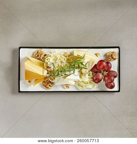 Wine Plate with Cheese Mix, Nuts and Grapes on White Rectangular Flat Plate Top View. Cheeseboard with Pieces of Various Cheese such as Cheddar, Manchego, Gauda and Smoked Cheese