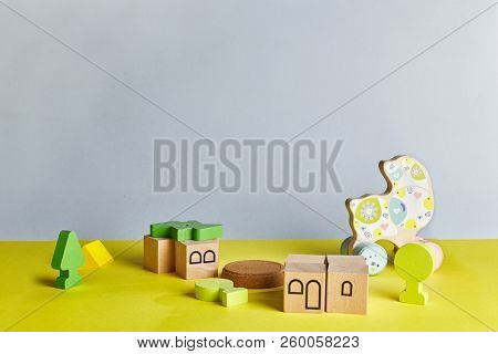 Abstract Kids Room Background with Natural Wooden Blocks and Toys. Children Room with Lime Green Floor and Grey Walls with Space For Text, Copyspace or Baby Products Mockup