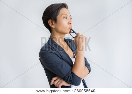 Pensive Asian Business Lady Touching Chin With Glasses. Young Lady Looking Away. Contemplation Conce