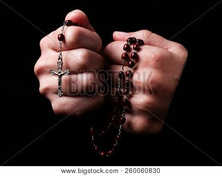 Female hands praying holding a rosary with Jesus Christ in the cross or Crucifix on black background. Woman with Christian Catholic religious faith
