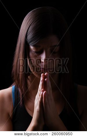 Faithful athletic woman praying, with hands folded in worship to god, head down and eyes closed in religious fervor, on black background. Concept for religion, faith, prayer and spirituality