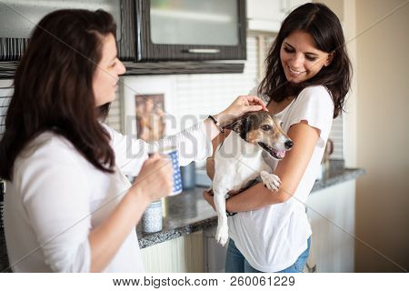 Happy free time with beloved dog. Beautiful young woman and friend staying indoor smiling and holding cute Jack Russell. Happy pets friendship emotion concept poster