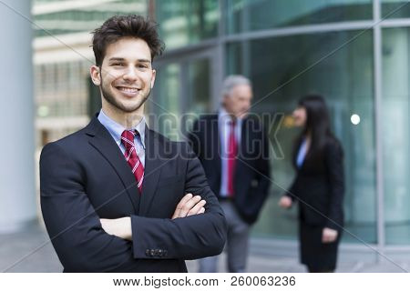 Smiling young businessman in front of his business group