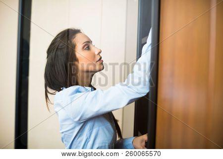 Businesswoman taking a folder from a closet