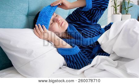 Portrait Of Sick Woman After Hangout Suffering From Headache Putting Cold Wet Towel On Forehead
