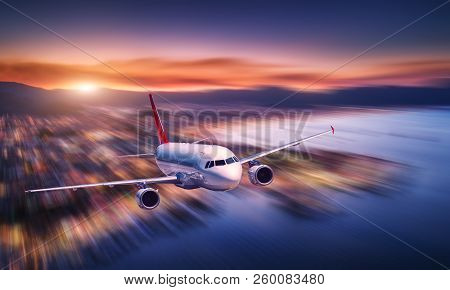 Airplane With Motion Blur Effect Is Flying Over Sea Coast At Night. Landscape With Passenger Airplan