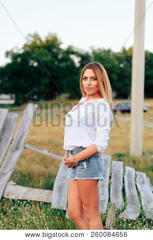 Young Beautiful Blonde In A White Shirt And Short Denim Shorts Outdoors