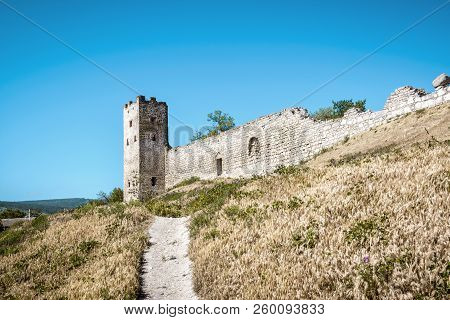 Old Genoese Fortress In Feodosia, Crimea, Russia. Panorama Of The Fortress Ruins With A Path In Summ