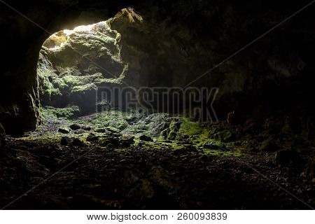 Dark Cave With A Bright Daylight Spot Of Exit. Natural Cave Opening In Crimea. Entrance To The Karst