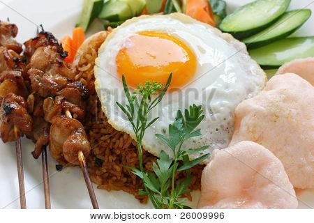 nasi goreng with prawn crackers and chicken satay , indonesian dish