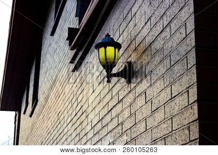 Lamp Mounted On A Brick Wall Illuminating Golden Light In The Morning Hues