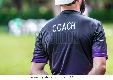 Back View Of Male Soccer Or Football Coach In Dark Shirt With Word Coach Written On Back, Standing O