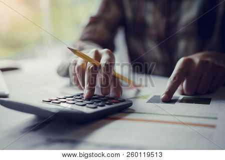 Businesswoman Holding A Pencil To Analyze The Marketing Plan With Calculator On Wood Desk In Office.