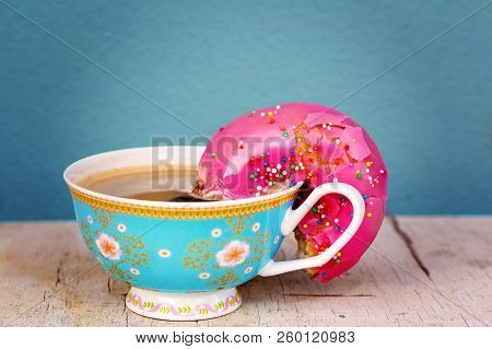 Pink Glazed Doughnut With Colorful Sprinkles Soaking Up Coffee From A Pink Floral Cup - Conceptualiz