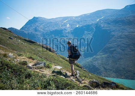 Male Hiker With Backpack Walking On Besseggen Ridge Over Gjende Lake In Jotunheimen National Park, N