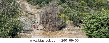 Woman And Teen Running On Ancient Pathway On Philopappos Hill In Central Athens