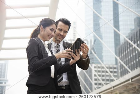 Business Man And Business Woman Partner Using Tablet Connection Social Media For Work.
