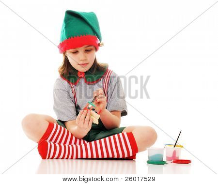 A Christmas elf painting a little wooden train engine for Santa to give on Christmas Eve.  Isolated on white.