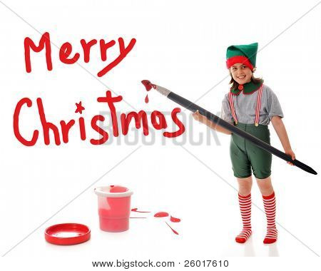 """A young girl dressed as Santa's Elf, painting a red """"Merry Christmas"""" sign with an over-sized artist's brush.  She's surrounded by paint spatters, a plastic bucket and lid."""