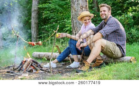 Couple Romantic Date Near Bonfire In Forest. Couple Relaxing Sit On Log Having Snacks. Hike Picnic D