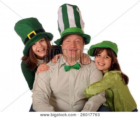 A family portrait of a dad and his two daughters celebrating St. Patrick's day wearing green and weary goofy, over-sized hats.  Isolated on white.