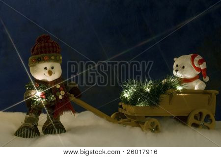 A plush snowman with a flashlight at night, pulling a wagon filled with Christmas lights, greenery and a white teddy bear over snow.