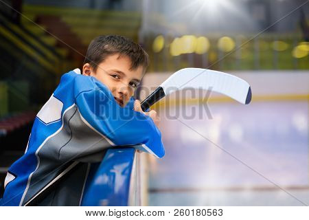 Young Hockey Player Standing Behind Rink Boards
