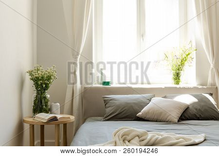 Sunny Morning In A Natural Style Bedroom Interior With A Bed, A Night Table And A Bunch Of Wild Flow