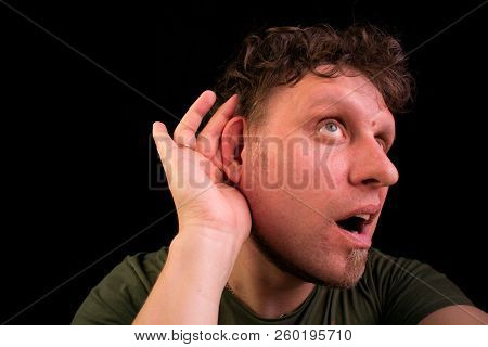 The Person Listens Very Attentively. He Pushes His Ear And Listens. His Face Is Surprised And Deligh