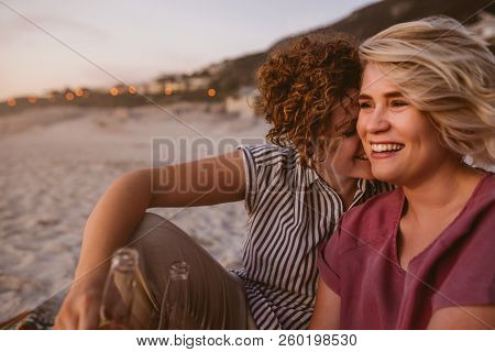 Young Lesbian Couple Having Drinks While Watching A Beach Sunset