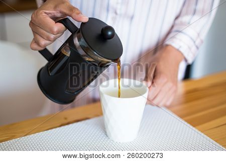 Close Up Of Female Hands Pouring Coffee From French Press