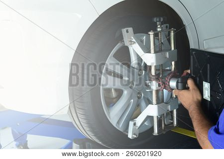 The Mechanic Install A Tool With The Wheel  During  The Step Of Wheel Alignment  At Service Center