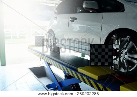 The Mechanic Install The Tool With The Wheel Of The Car That Parked On The Pedestal During The Proce