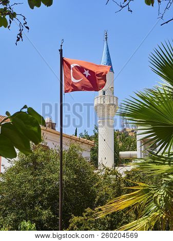 Minaret Of Kelerlik Mahallesi Cami Mosque With The Flag Of Turkey Waving In Foreground.