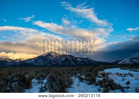 Wide Angle Dramatic Sky Above Desert Scene Golden Hour Sunset Peaks Above Taos New Mexico Winter Sno