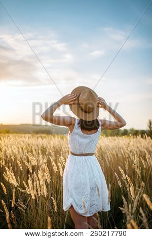 Woman in dress walking in wheat field on sunset