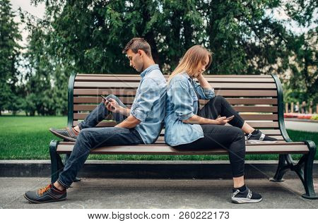 Phone addicted people, couple on the bench