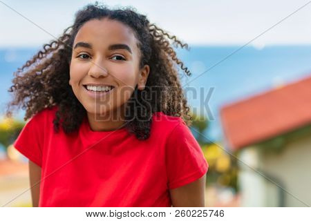 Outdoor portrait of beautiful happy mixed race African American girl teenager female young woman smiling with perfect teeth and the sea coastline behind her