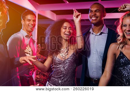 Cheerful girl dancing at night party with her friends. Beautiful young woman and smiling men having fun at nightclub. Group of multiethnic young people at club having fun at new year's eve.