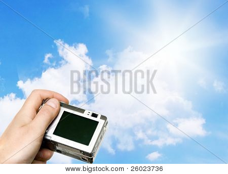 Digital point and shoot camera against blue sky