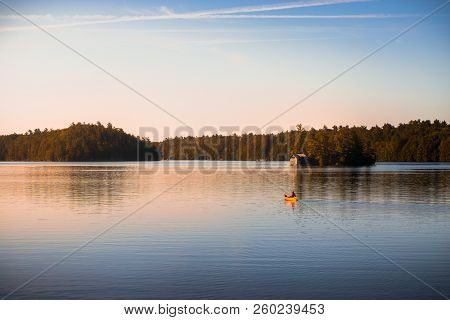 Canoe On Tranquil Lake Joseph, Muskoka, At Sunrise.